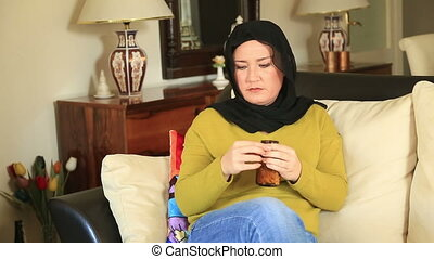 Muslim woman taking pill - Muslim woman taking medication at...