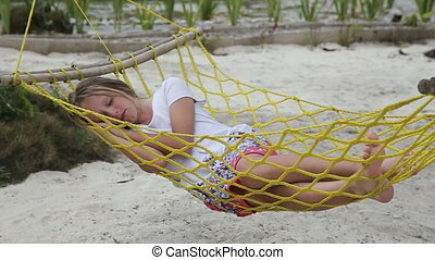 Young girl relaxing in a hammock on the sea beach