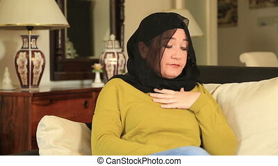 Muslim woman using asthma inhaler - Muslim woman seated on a...