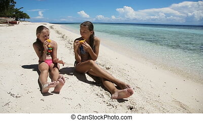 Young girls on the beach eating mango fruit - Two girl...