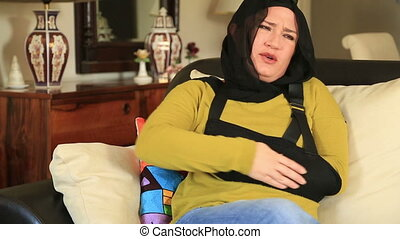 Muslim woman with a broken arm wearing arm brace