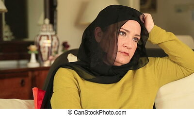 Sad muslim woman sitting on a sofa - Thoughtful muslim woman...