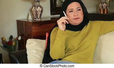 Sad muslim woman smoking cigarette