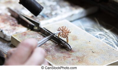 Assembly, soldering pieces of gold jewelry jeweler