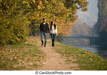 Couple Walking In Forest Through The Woods Outside During...
