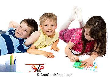 Three Children Drawing on Floor - Three children happily...