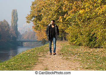 Attractive Man Walking In Autumn Forest - Young Man Walking...