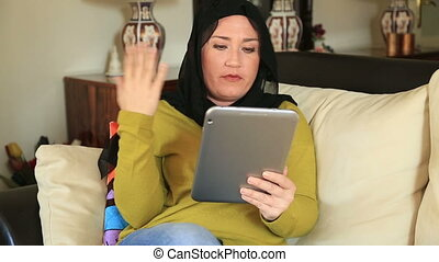 Video Telephony on Digital Tablet - Muslim woman sitting in...
