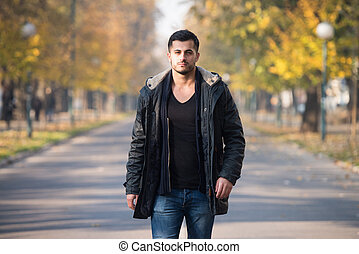 Man In Autumn Park - Young Man Walking In Forest Through The...