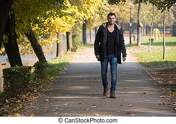 Young Man Walking In Autumn Forest - Young Man Walking In...
