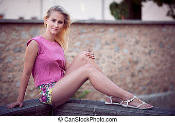 Beautiful young blonde woman on a walk arownd the city near...