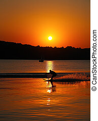 silhouette of man on water skis at sunset