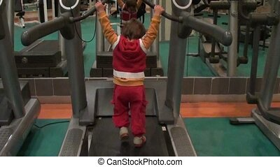 Toddler works out on running machine