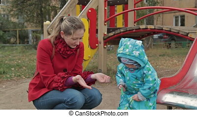 Little boy play with her mother with toy car in playground,...