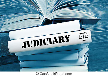 Book with Judiciary word on table in a courtroom or...