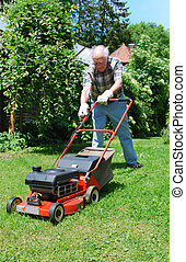 man with lawn mower - senior man mowing the grass wit a lawn...
