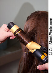 Curling Hair - Brown hair is curled by a curler before a...