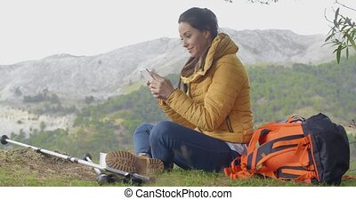 Smiling female hiker using her phone - Beautiful smiling...