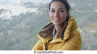 Smiling young woman hiking in the mountains sitting on the...