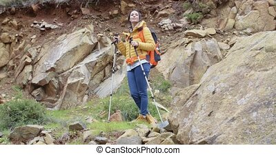 Healthy fit young woman outdoors backpacking in the...