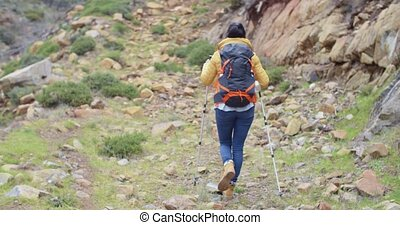 Rear view of an active female hiker striding along a...