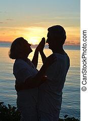 elderly couple on beach at sunset