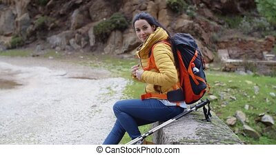 Smiling young woman on a mountain trail - Smiling young...