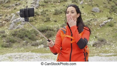 Smiling young backpacker using a selfie stick to take her...