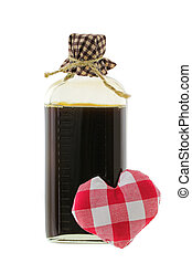 A glass bottle of love potion in brown with a red gingham heart