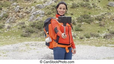 Young woman hiker using a selfie stick - Young woman hiker...
