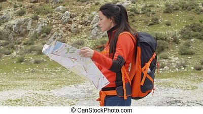 Young woman hiking using a map - Young woman hiking in the...