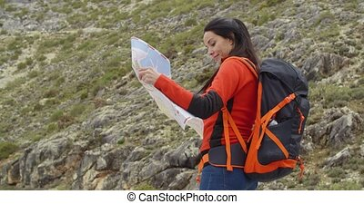 Young woman out hiking checking a map