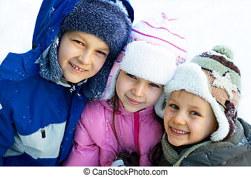 Kids Playing On a Winter Day - Three happy children, dressed...