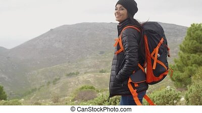 Happy smiling woman enjoying a misty hike in the mountains...