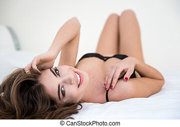 Sexy woman in lingerie relaxing on the bed - Happy sexy...