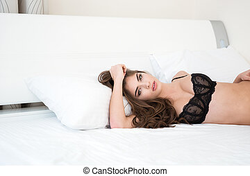 Sexy woman in black lingerie lying on the bed