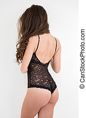 Young woman standing in sexy bodysuit - Back view portrait...