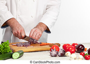 Chef cutting a onion on his kitchen - The hands of chef...