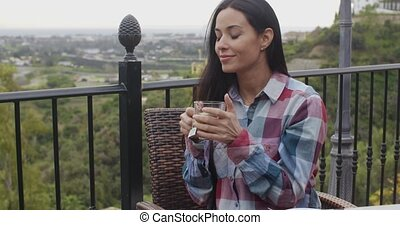 Smiling young woman relaxing outdoors with tea - Smiling...