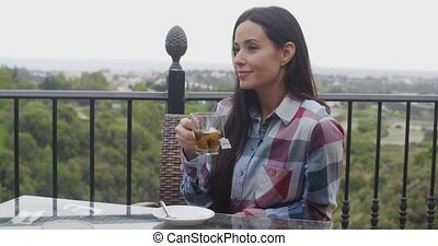 Young woman enjoying a hot cup of tea at an open air...