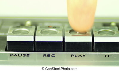 Pushing a finger play button on a tape recorder.