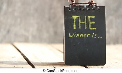 The Winner Is... card - The Winner Is... text. Chalk...