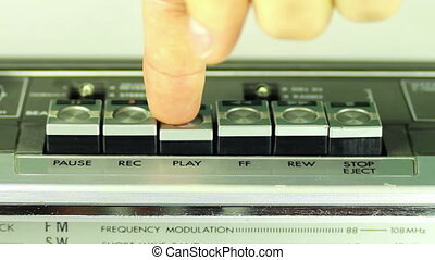 Pressing a finger play button on a tape recorder.