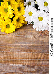 White and yellow oxeye daisy flowers bouquet on wooden...