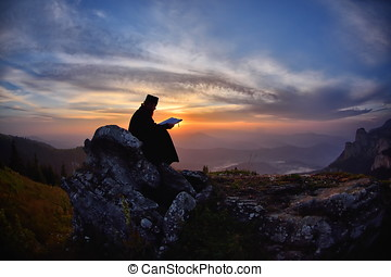 silhouette of priest reading in the sunset light, Romania, Ceahlau