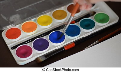 Watercolor painting Brush taking watercolor on color palet