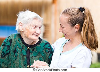 Elderly woman with caregiver - Photo of elderly woman with...