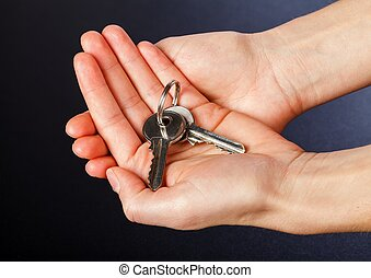 House keys - Photo of house keys in hands on isolated black...