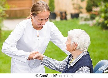 Elderly care - Photo of young carer helping the elderly...
