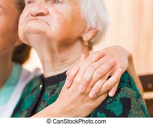 Elderly woman - Photo of young caregiver hugs the elderly...